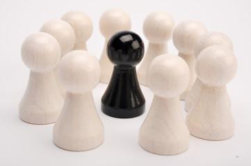 Schwarze Figur umkreist von weissen Figuren