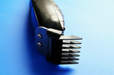 closeup of electric barber clippers, on blue poster