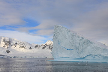 Iceberg and landscape in Antarctica with clouds in background