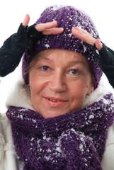 Eine reife und lachende Frau im Winter.