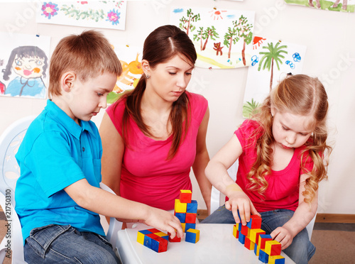 Children preschooler  with wood block  in play room.