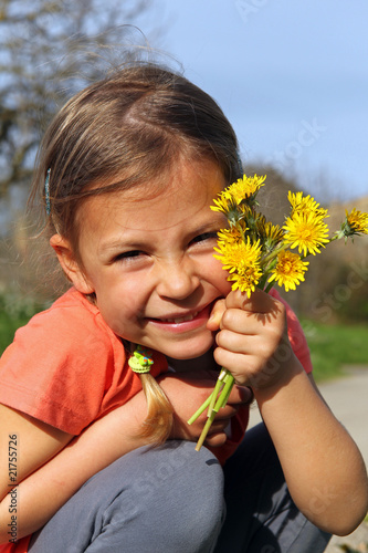 Cute young girl holding a bunch of yellow daisies