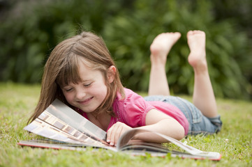 little girl laying in grass reading