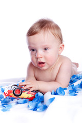 Baby boy playing with red car toy isolated on white