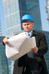 Engineer with blue hard hat holding drawing