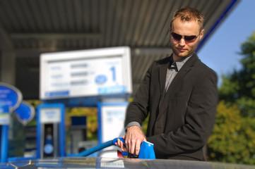 Junger Mann im Anzug tankt sein Auto auf