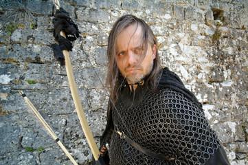 Bogenschütze Robin Hood vor Burgmauer