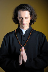 Praying priest with wooden cross