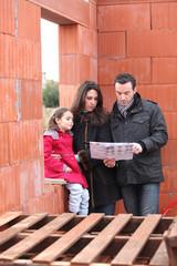 Famille sur un chantier d'une maison en construction