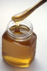 Honey Dripping from Wooden Server into Glass Jar