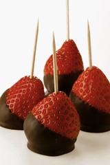 Chocolate-coated strawberries on toothpicks