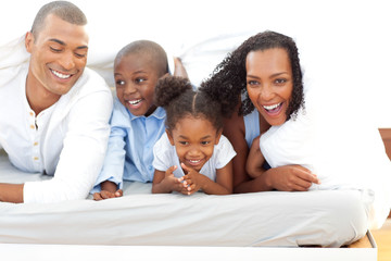 Lively family having fun lying down on bed
