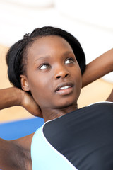 Ethniic woman in gym outfit doing sit-ups