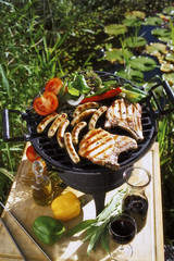 Pork chops, sausages & vegetables on barbecue in open air