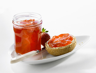 Strawberry jam on bread roll and in jar