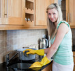 Smiling young woman cleaning in a kitchen