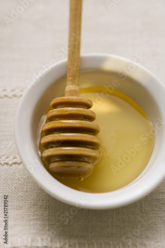 Honey dipper in a small bowl of honey