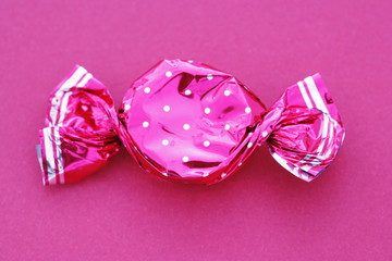 A sweet in a pink wrapper on a pink background