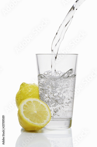 Pouring water into a glass & lemons