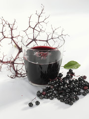A glass of elderberry & apple juice & fresh elderberries