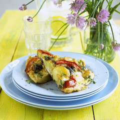 Two pieces of vegetable frittata on a pile of plates