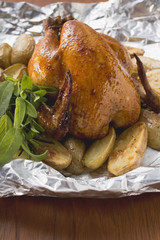 Roast chicken with potatoes and herbs on aluminium foil