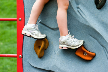 Closeup Child's Legs on Rock Wall