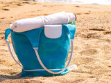 Pretty blue beach bag and accessories on sand poster