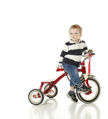 Boy Looking Uncertain, Getting Ready to Ride Tricycle