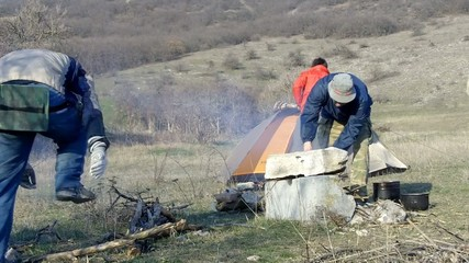 Hikers cook on a fire and build a camp