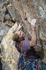 Rock climber reaching.