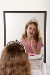 little girl playing lip gloss and fairy princess
