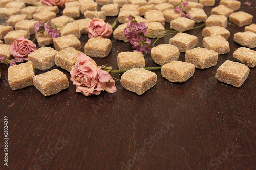 cane sugar and flowers on a grunge brown wooden table
