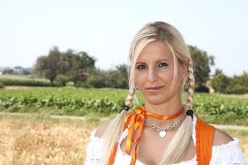 Frau in orangefarbenem Dirndl