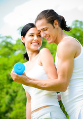 Young happy couple exercising with dumbbell, outdoors