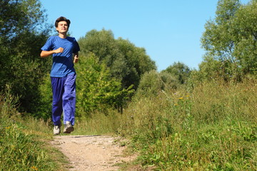 man wearing sporty clothes is running along path outdoor
