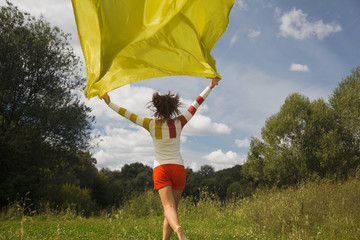 woman in day runnig with yellow fabric in hand, whiffle fabric