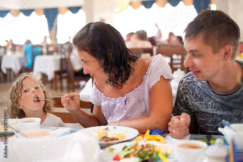 family having dinner together. mum feeds girl from plug.