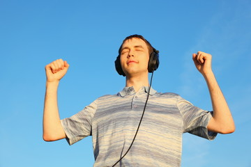 handsome man is listening music outdoors with closed eyes