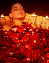 Beautiful girl in jacuzzi with rose petal and candle.