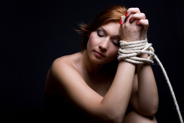 Beautiful red-haired woman tied with rope