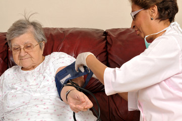 Mixed raced nurse measuring senior patient's blood pressure