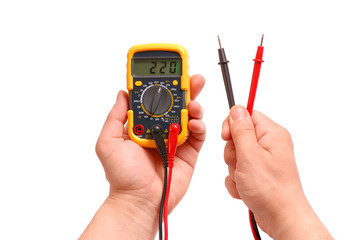 Hands with a digital multimeter on a white background