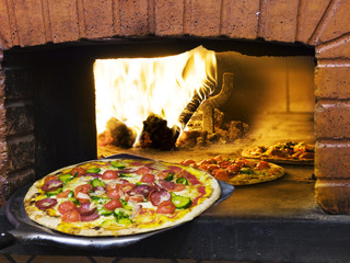 pizza coming out of a wood burning pizza oven.