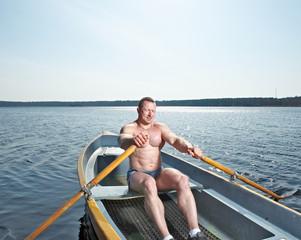 Muscular man with oars in boat