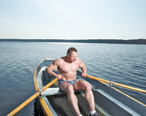 Muscular man with oars in boat