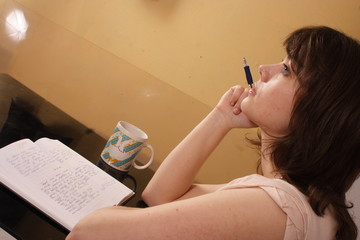 young beautiful woman writing in her diary