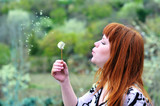 beautiful girl  blowing on dandelion