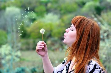 beautiful girl  blowing on dandelion
