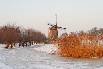 Windmill in Winter With A Frozen Canal